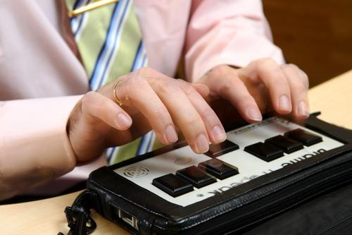 Foto de un Braille Hablado y unas manos que lo están manejando