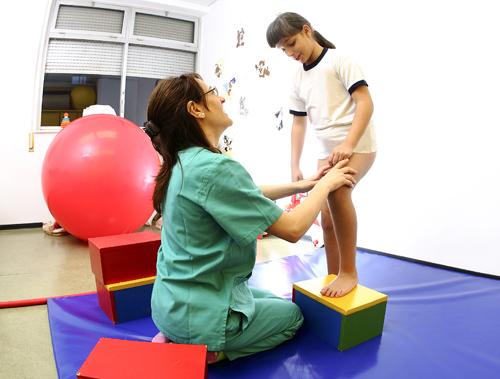 Una fisioterapeuta trabaja el área del desarrollo motor con una niña con discapacidad visual