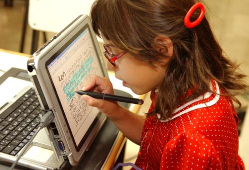 una niña con discapacidad visual escribe en una tablet pc