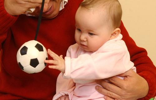 un adulto trabaja con una bebé el desarrollo de la coordinación ojo-mano a través de la manipulación de una pelota